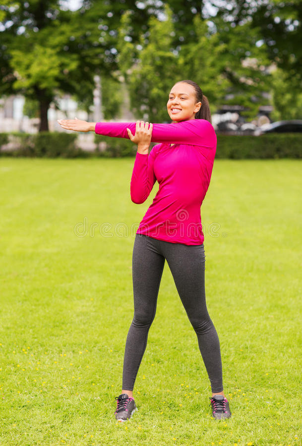 Smiling black woman stretching leg outdoors royalty free stock photos