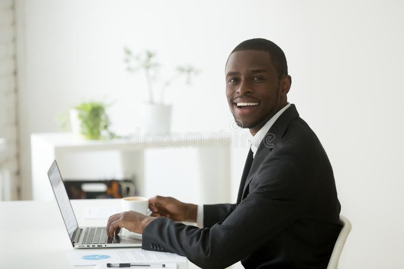 Smiling black worker working at laptop and drinking coffee royalty free stock photos