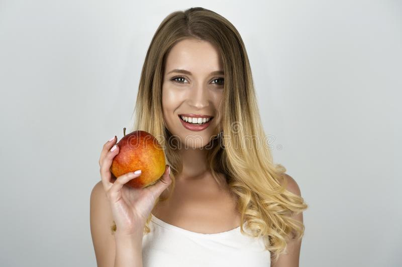 Smiling blond attractive woman holding juicy apple in one hand isolated white background stock photo