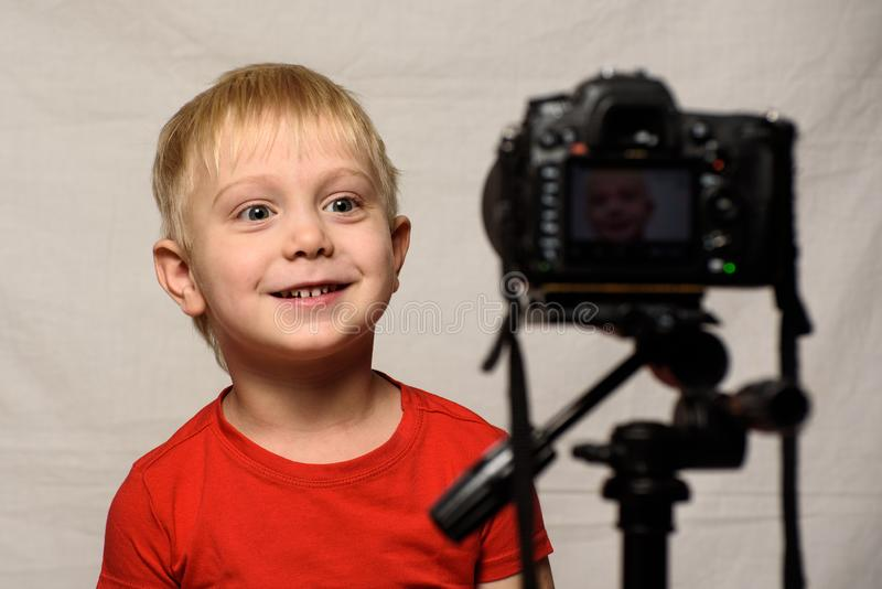 Smiling blond boy in front of the camera lens. Little video blogger. Home studio stock images