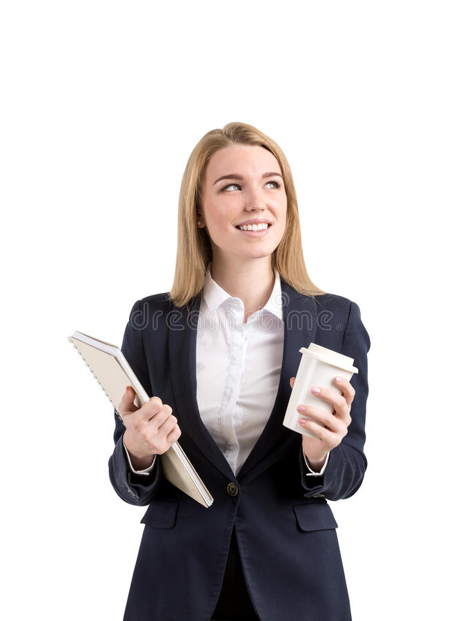 Smiling blond businesswoman with a notebook and a cup of coffee royalty free stock images