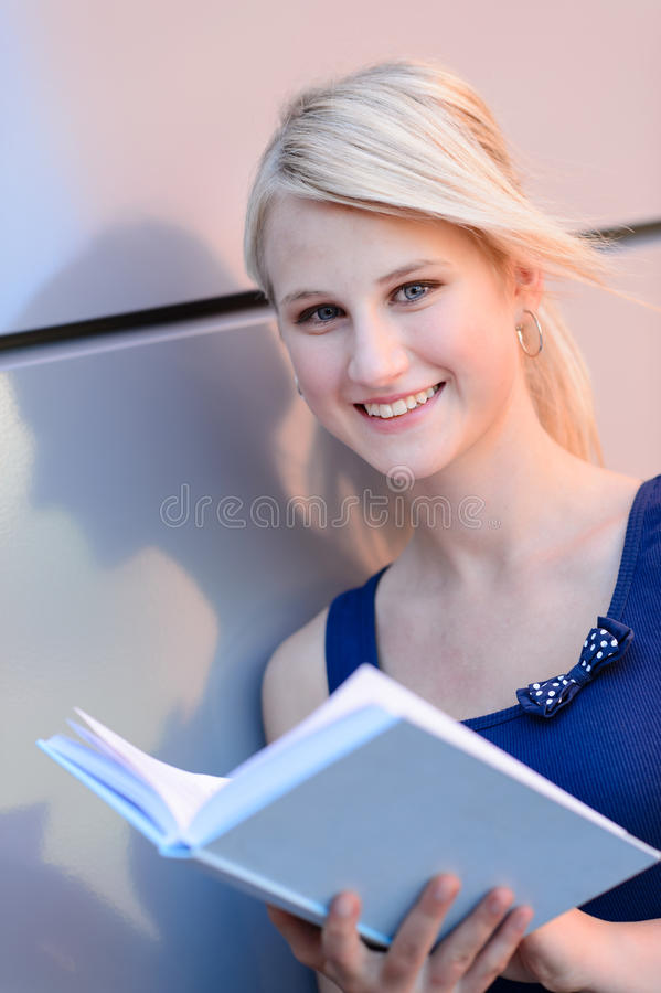 Smiling blond college student girl open book royalty free stock photos