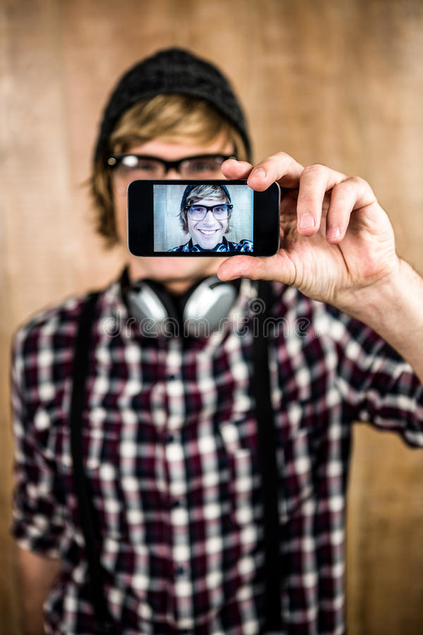 Smiling blond hipster taking selfie. With wooden background royalty free stock image