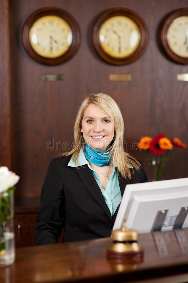 Smiling blond receptionist. Behind the counter in hotel royalty free stock photography
