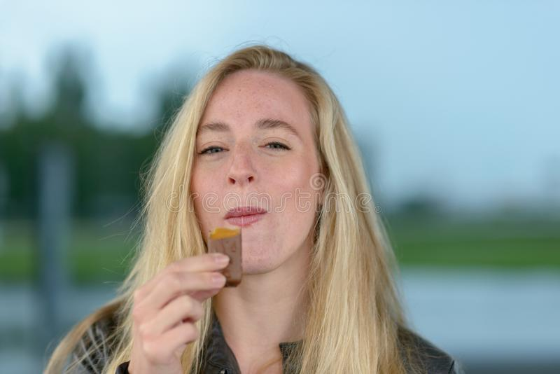 Smiling blond woman eating chocolate stock images
