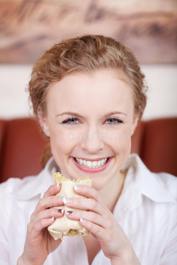 Smiling blond woman eating wrap royalty free stock photo