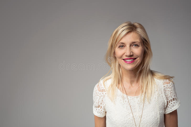 Smiling Blond Woman on Gray with Copy Space stock photo