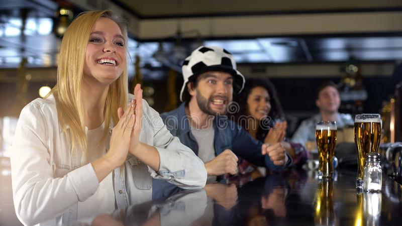 Smiling blond woman happy about sports game results, fans watching match in pub. Smiling blond women happy about sports game results, fans watching match in pub royalty free stock image
