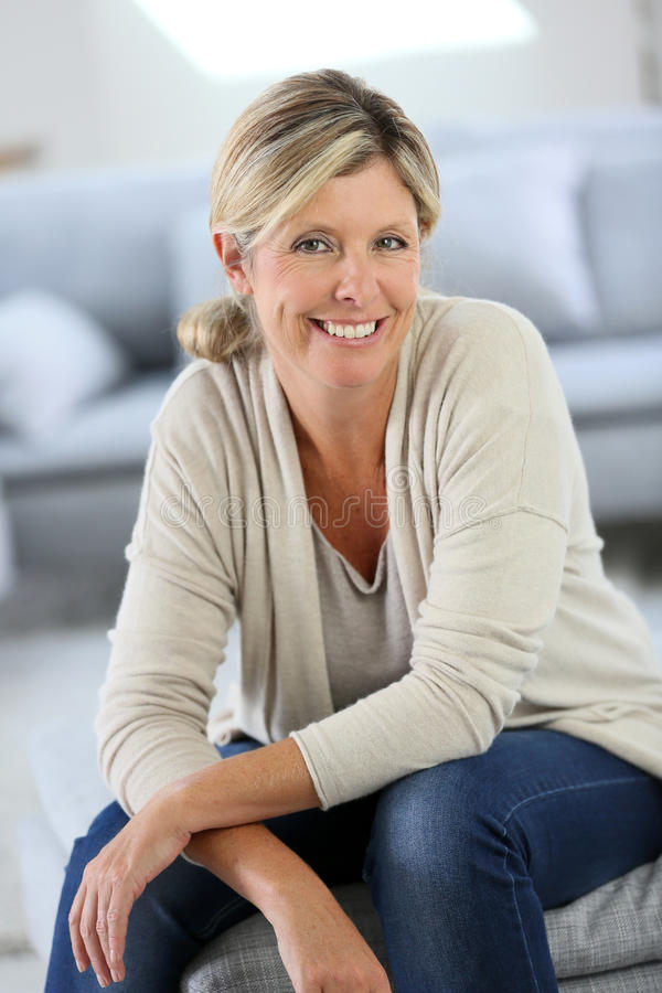 Smiling blond woman at home stock photo