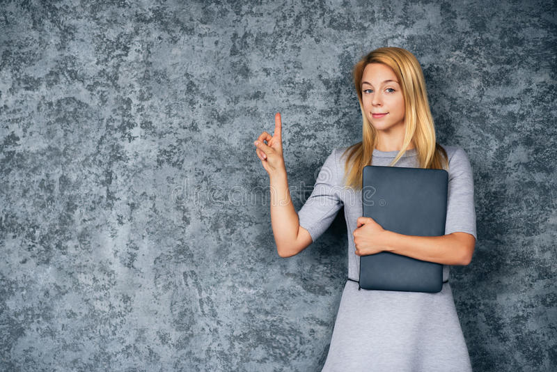 Smiling blond woman with laptop over gray background. Woman holding laptop and showing attention please concept over gray wall. Looking at camera stock photography