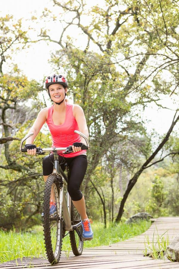 Smiling blonde athlete mountain biking royalty free stock image