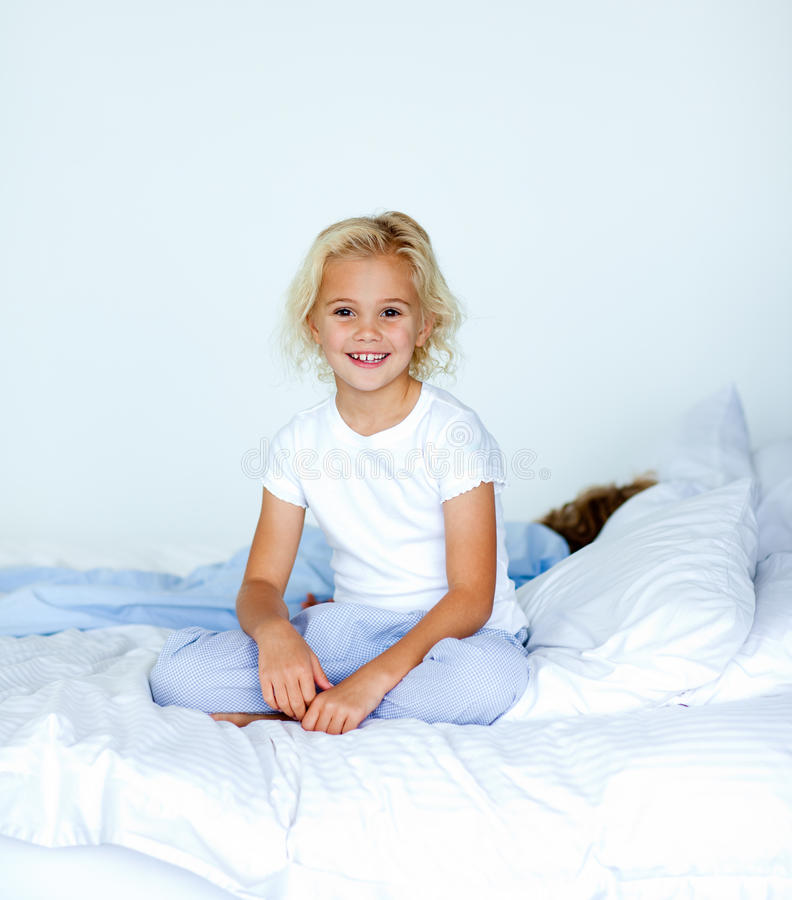 Download Smiling Blonde Girl Sitting On A Bed Stock Photo - Image: 9652582