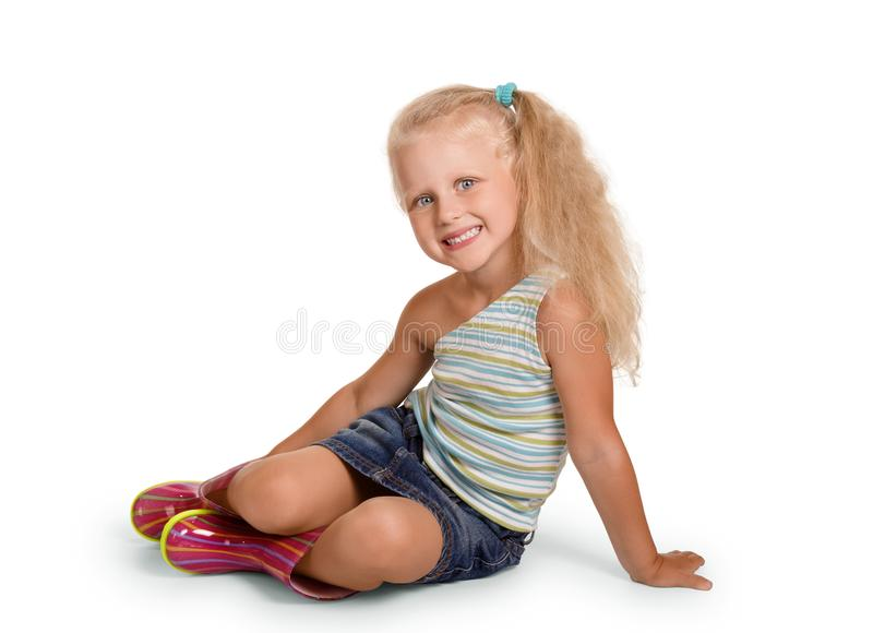 Smiling blonde girl sitting in rubber boots, isolated on white stock photos