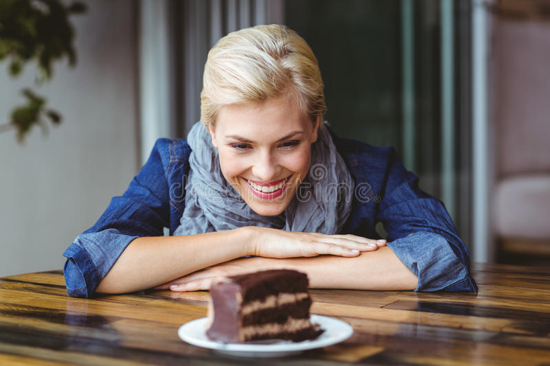 Smiling blonde looking a chocolate cake. At the cafe royalty free stock photo