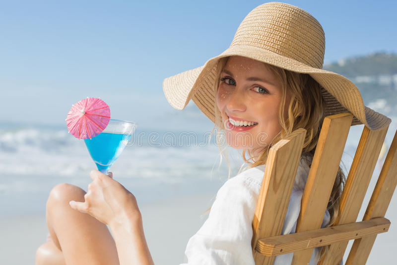 Smiling blonde relaxing in deck chair by the sea holding cocktail royalty free stock photography