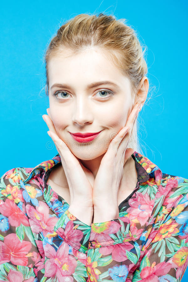 Smiling Blonde with Sensual Lips and Perfect Skin Wearing Colorful Shirt on Blue Background in Studio. Body Care Concept royalty free stock photography