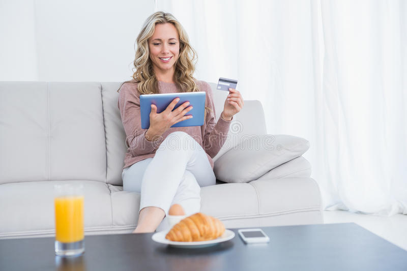 Smiling blonde sitting on couch shopping online. At home in the living room stock photos