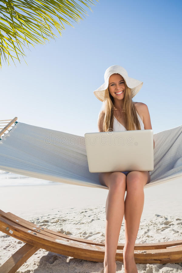 Smiling Blonde Sitting On Hammock Using Laptop Royalty Free Stock Images