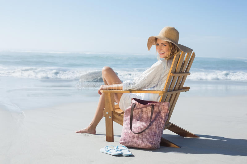 Smiling blonde sitting on wooden deck chair by the sea stock image