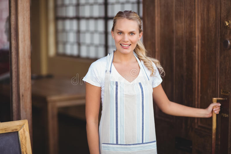 Smiling blonde waitress opening the door royalty free stock images