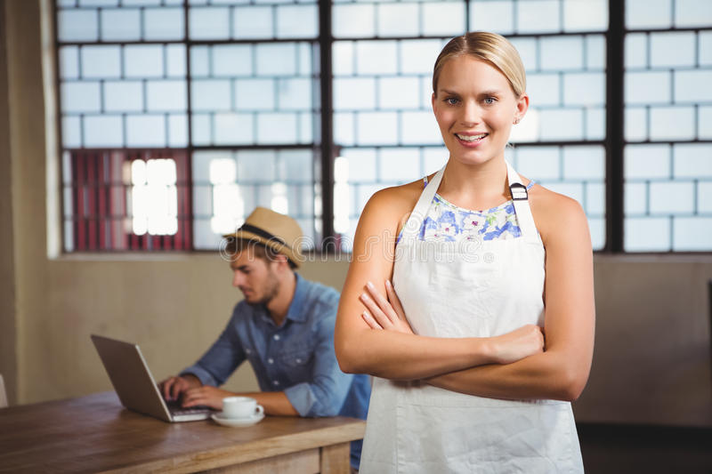 Smiling blonde waitress posing in front of customer stock image