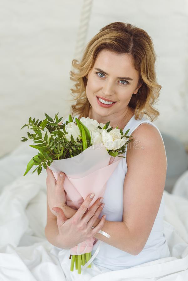smiling blonde woman with bouquet of flowers for 8 stock photography