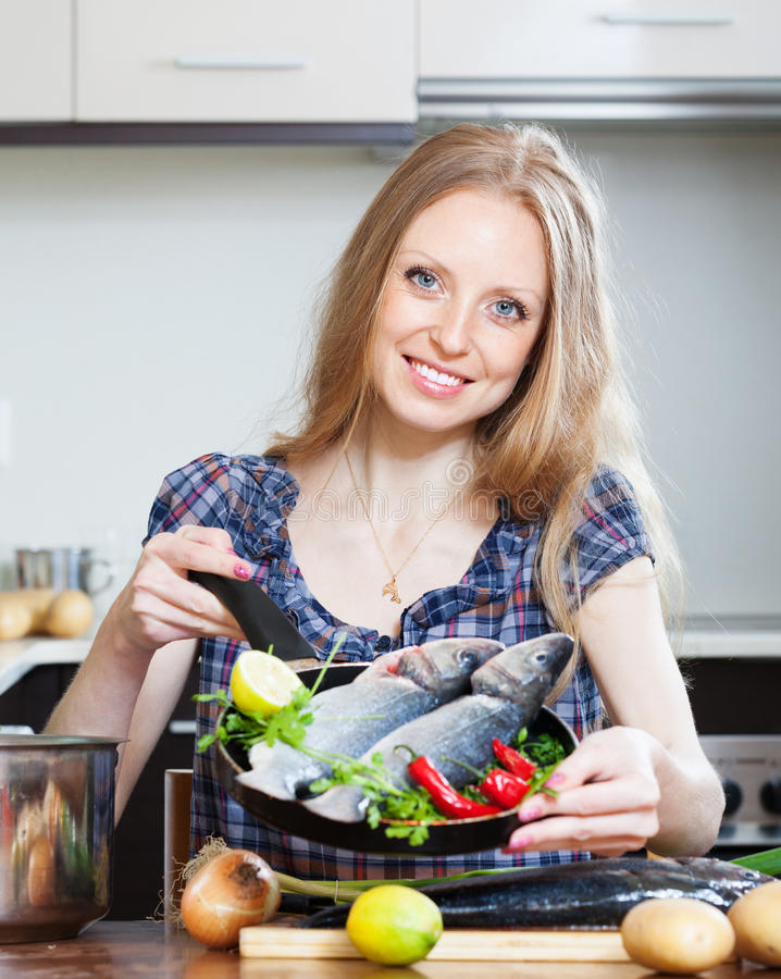 Smiling blonde woman cooking lubina in frying pan. At domestic kitchen stock photo
