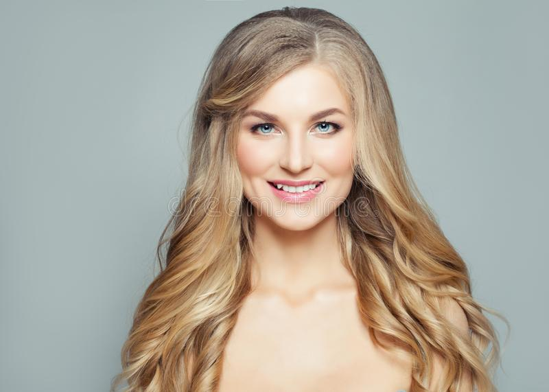 Smiling blonde woman with curly hair and clear skin. Fashion portrait royalty free stock image