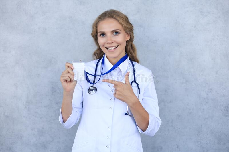 Smiling blonde woman doctor wearing uniform standing isolated over grey background, showing her name on badge stock images