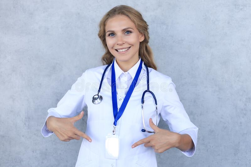 Smiling blonde woman doctor wearing uniform standing isolated over grey background, showing her name on badge stock photo
