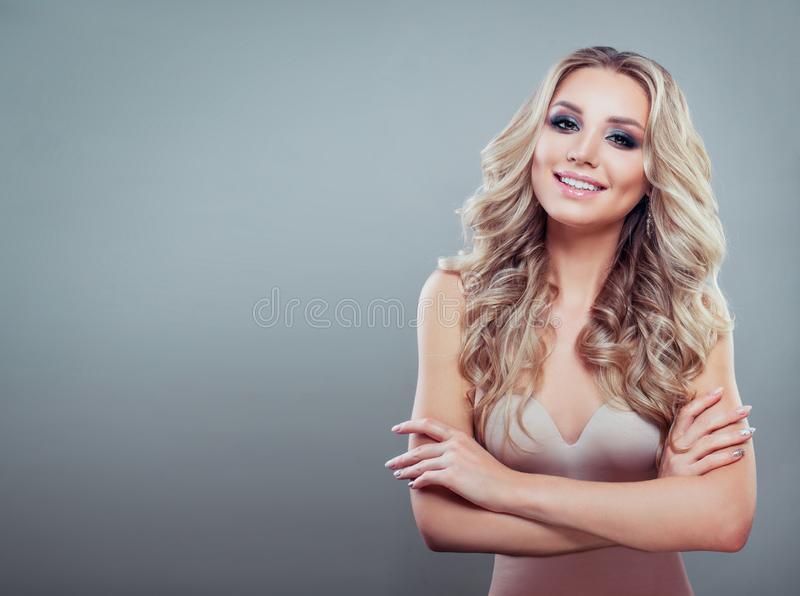 Smiling blonde woman with healthy wavy hair and makeup. On blue background with copy space royalty free stock image