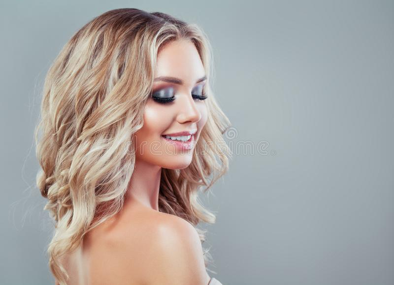 Smiling blonde woman with healthy wavy hair. And makeup on blue background stock image