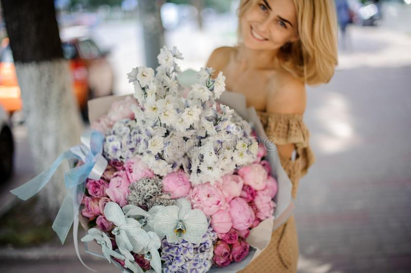 Smiling blonde woman holding a big bouquet of various flowers stock images