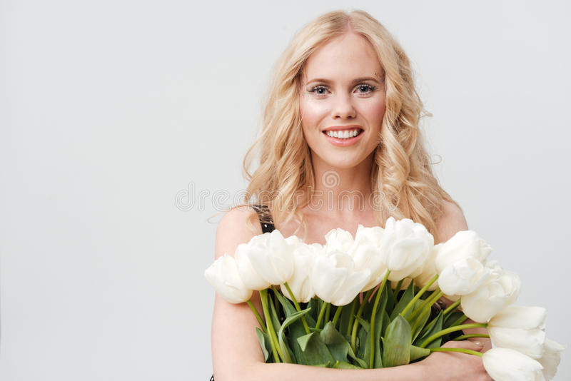 Smiling blonde woman holding bouquet of flowers stock photography