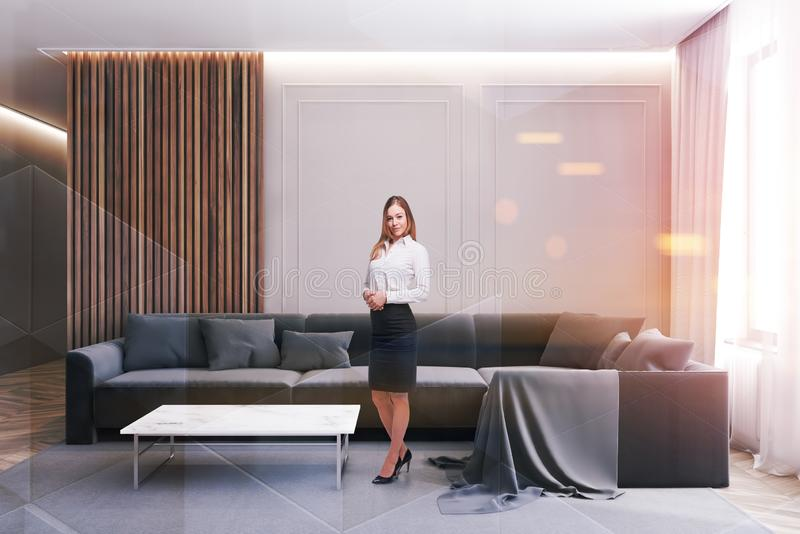 Smiling blonde woman in modern living room. Charming blonde woman in business suit standing in luxury living room interior with white and wooden walls royalty free stock photography