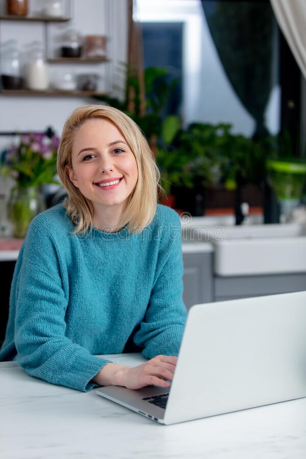 Blonde woman with notebook computer sitting at kitchen. Smiling blonde woman with notebook computer sitting at kitchen royalty free stock photography