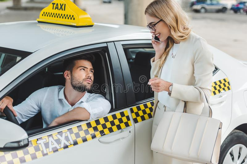smiling blonde woman talking by smartphone and looking at male driver sitting stock photography