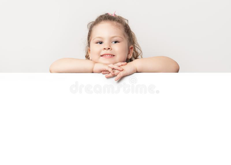 Smiling blue eyed little girl peeking behind a white board royalty free stock images