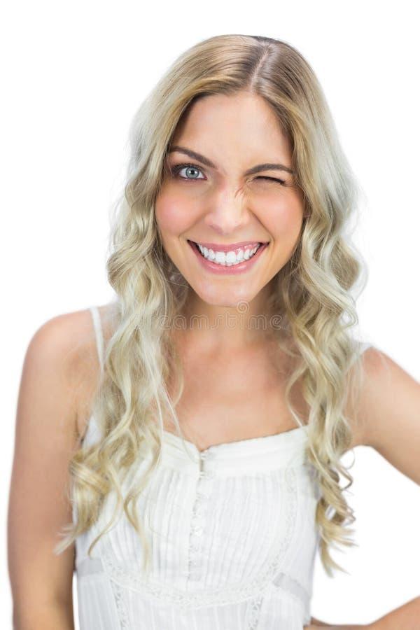 Smiling blue eyed model winking at camera royalty free stock photography