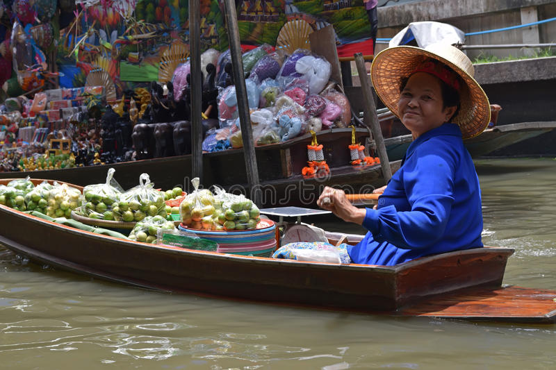 Smiling Boat vendor selling green fruits while rowing nearby floating market around Bangkok area stock photography