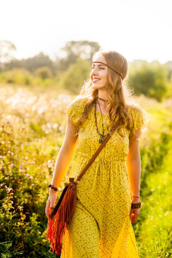 Smiling bohemian girl in yellow dress on the field at sunset warm light stock images