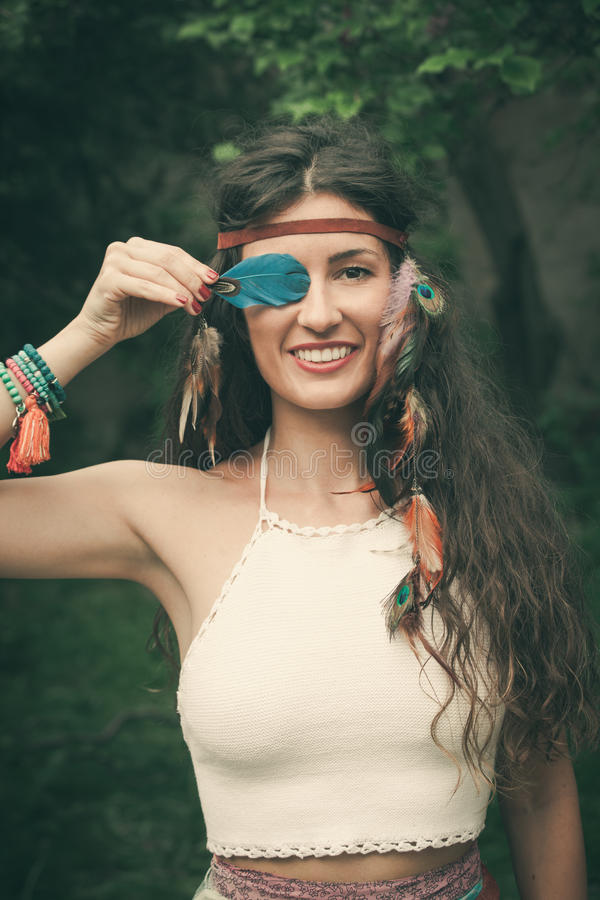 Smiling bohemian style fashion girl outdoor. Smiling young bohemian fashion style woman with feather portrait closeup royalty free stock photos