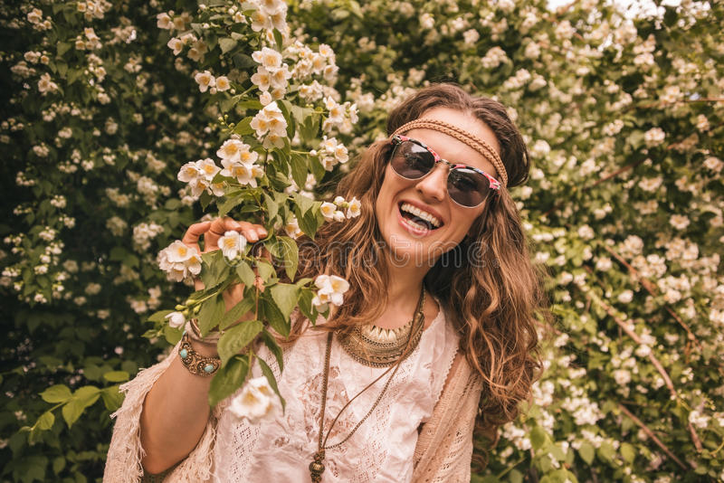Smiling bohemian young woman holding branch of flowers. Longhaired hippy-looking young lady in knitted shawl and white blouse standing among flowers royalty free stock photos