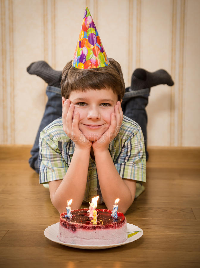 Smiling boy with birthday cake on the floor. Smiling boy with birthday cake lying on the floor stock photography