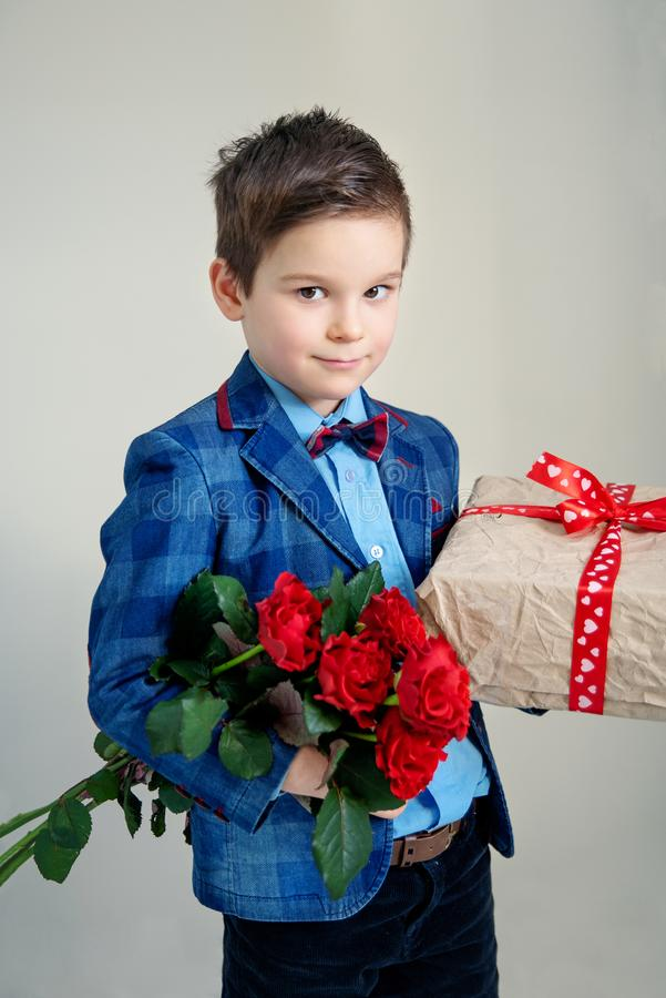 Smiling boy with bouquet of flowers and a gift on a light background royalty free stock photography