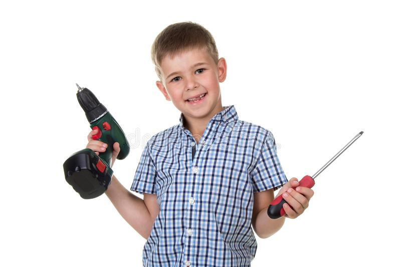 Smiling boy builder in checkered shirt holds a drill and a screwdriver in his hands, isolated on white background royalty free stock photos