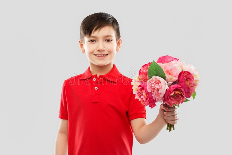 Smiling boy with bunch of peony flowers stock images