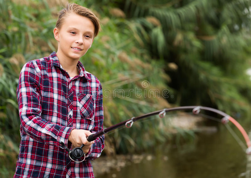 Smiling boy casting line for fishing on lake stock photos