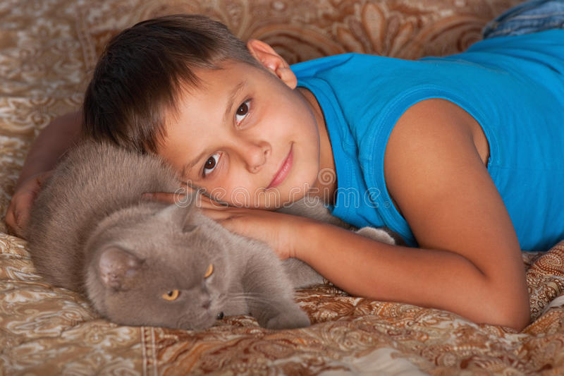 Smiling boy with a cat. A smiling boy is hugging his cat stock images
