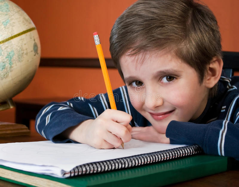Smiling boy doing homework. Cute boy with paper and pencil doing homework, soft focus portrait royalty free stock photos